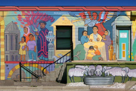 "The mural on Trinity's building at 20th and Riverside Is filled with biblical figures. The artist, Larry Rostad, wrote: ""We have represented the extended family of faith with paint, in mural form …. Our hope is that Trinity's mural will contribute to our neighborhood; may visible hand-painted images help reveal the INVISIBLE things of the Spirit."""